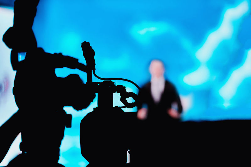 Camera Recording Presentation of a Speaker Media Press Conference Silhouette Camera Speaker News Reportage Presentation Communication Public Event Technology Equipment Speech Meeting Seminar Television Politician Politics Entertainment Bussiness Jurnalist Government Stage Corporate Live Leadership Campaign Correspondent Broadcast Blue People Stage - Performance Space Standing Indoors  Unrecognizable Person
