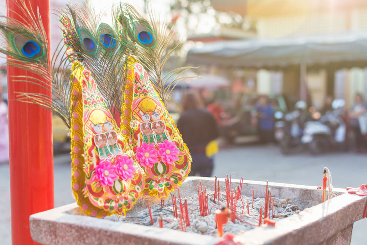 Peacock feathers and religious offerings outside temple