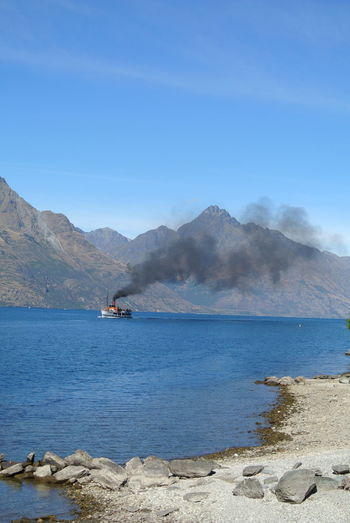 Calm Holiday Old-fashioned Smoke Beauty In Nature Blue Blue Sky Boanoite Boat Lake Lake View Mountain Mountain Range Mountains Nature New Zealand No People Outdoors Queenstown Rocks Rocks And Water Scenics Sky Tranquility Water