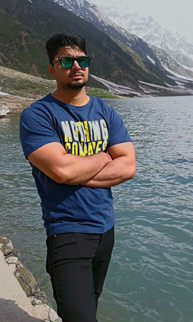 sunglasses, casual clothing, one person, standing, mid adult, day, arms crossed, real people, lake, outdoors, looking at camera, only men, mature adult, cap, smiling, one man only, water, portrait, mountain, young adult, men, happiness, nature, adult, adults only, people