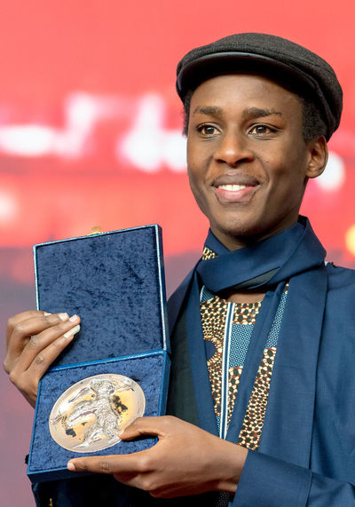 Berlin, Germany - February 24, 2018: Samuel Ishimwe, winner of the Silver Bear Jury Prize (Short Film) for the movie 'Imfura', poses at the Award Winners press conference during the 68th Berlinale AWARD Closing Ceremony Film Festival Arts Culture And Entertainment Berlinale Berlinale 2018 Berlinale Festival Berlinale2018 Cap Close-up Entertainment Entertainment Event Holding Imfura Indoors  Looking At Camera Mass Media One Person Portrait Prize Samuel Ishimwe Smiling Winner Young Adult