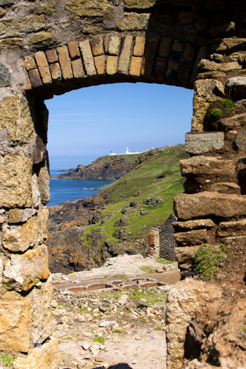 Pendeen Lighthouse as Seen from Geevor Mine, Cornwall UK Lighthouse Pendeen Arch Clear Sky Day Geevor Mine History Lighthouse_lovers Lighthousephotography Outdoors Poldark Rock - Object Scenics - Nature Sky Stone Wall Tranquility Wall Water