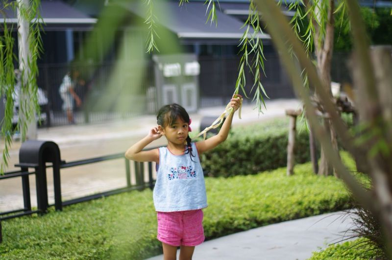Full length of girl with plants in foreground