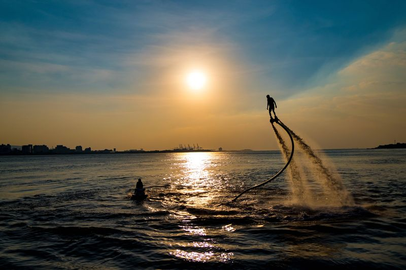 Silhouette man flyboarding on sea against sky during sunset