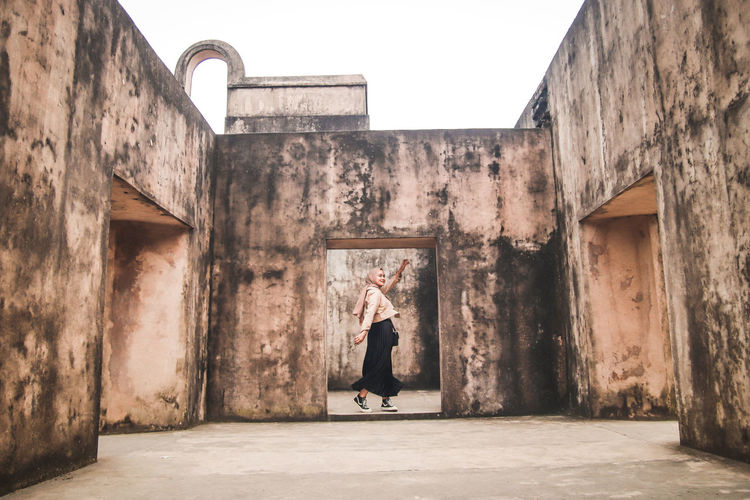 Woman standing by building