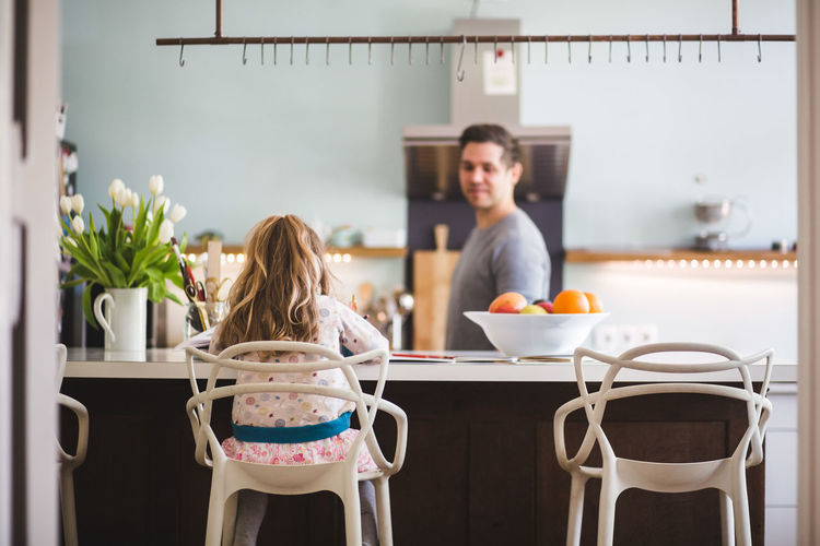 Rear view of couple sitting on table