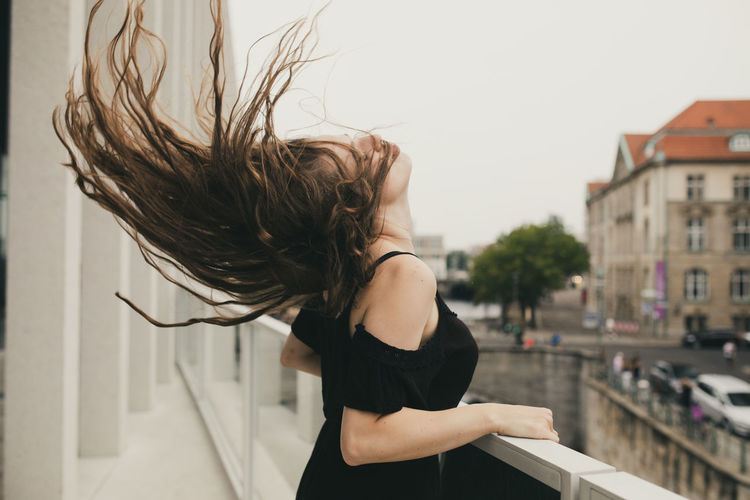 Young woman tossing hair while standing against building