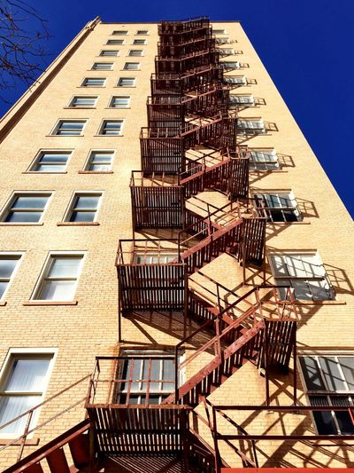 Architecture Built Structure Building Exterior Steps Low Angle View Railing Steps And Staircases Fire Escape Outdoors No People Sky Day Petroleum Building Sunlight And Shadow Urban Exploration