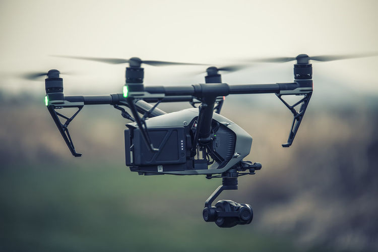 Close-up of quadcopter flying against sky