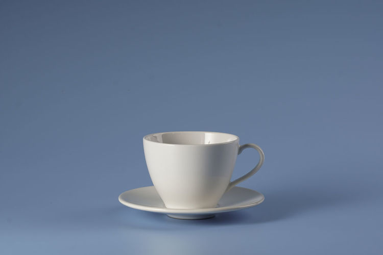 Close-up of coffee cup on table against blue background