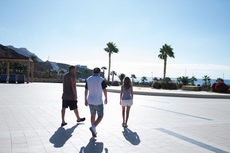 Adult Footpath Full Length Group Of People Leisure Activity Lifestyles Men Nature Outdoors Palm Tree People Plant Real People Rear View Shorts Sky Sunlight Togetherness Tree Tropical Climate Vacation Destination Walking Women