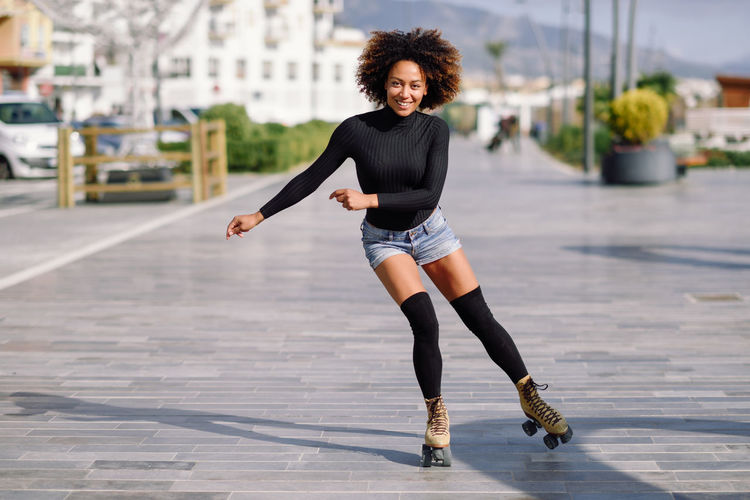 Young fit black woman on roller skates riding outdoors on urban street. Smiling girl with afro hairstyle rollerblading on sunny day Afro Afrohair Beautiful Woman City Day Focus On Foreground Full Length Happiness Leisure Activity Lifestyles Looking At Camera One Person Outdoors Portrait Real People Rollerblading Rollerskating Skates Skating Smiling Young Adult Young Women