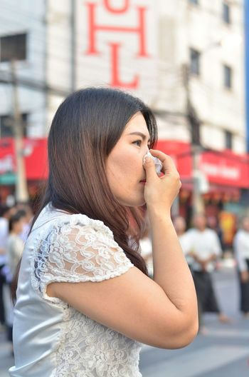 Side view of woman blowing nose while standing on road in city