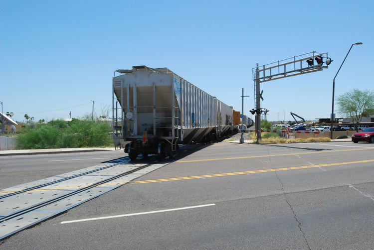 Freight train leaving a railroad crossing in Mesa, AZ Blue Car City Street Clear Sky Day Diminishing Perspective Empty Freight Transportation Gates Industry Land Vehicle Mode Of Transport No People Outdoors Railroad Road RR Crossing Sky Street Sunlight Sunny Train Tracks Trains Transportation