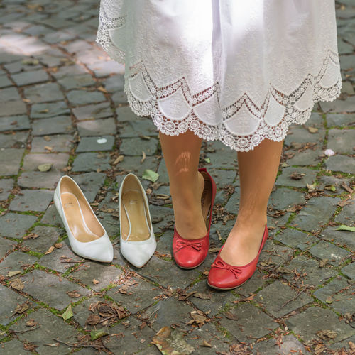 A detail of a bride changing shoes in the wedding dress outdoors in a park.