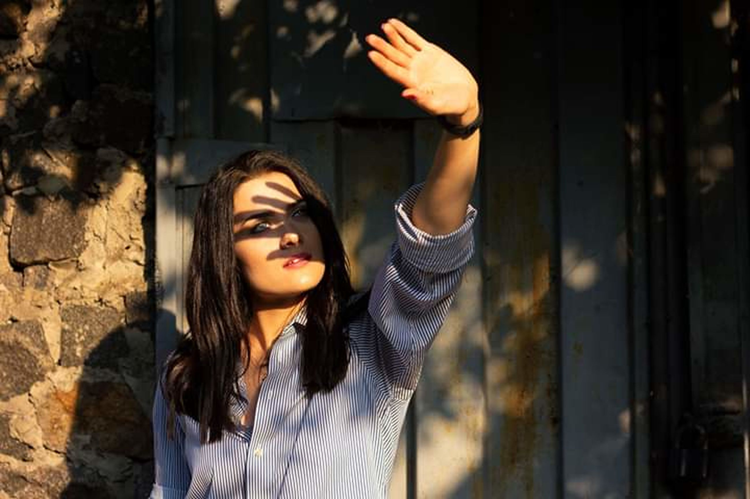 one person, portrait, headshot, young adult, beauty, arms raised, standing, looking, hair, women, beautiful woman, hairstyle, adult, human arm, brown hair, sunlight, body part, long hair, outdoors, human limb, contemplation, hand raised, brick