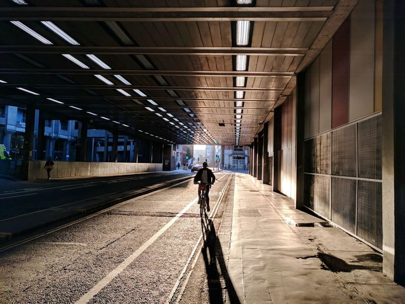 Contrasty backlighted men riding a bicycle in tunnel EyeEm Best Edits Streetphotography London Editorial  Shadow EyeEm Selects Sunny Backlight Bicycle Tunnel Barbican Light And Shadow Natural Light HDR Walking Architecture