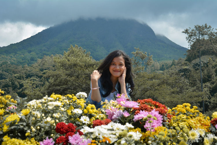 Portrait of smiling woman by flowering plant against mountain range