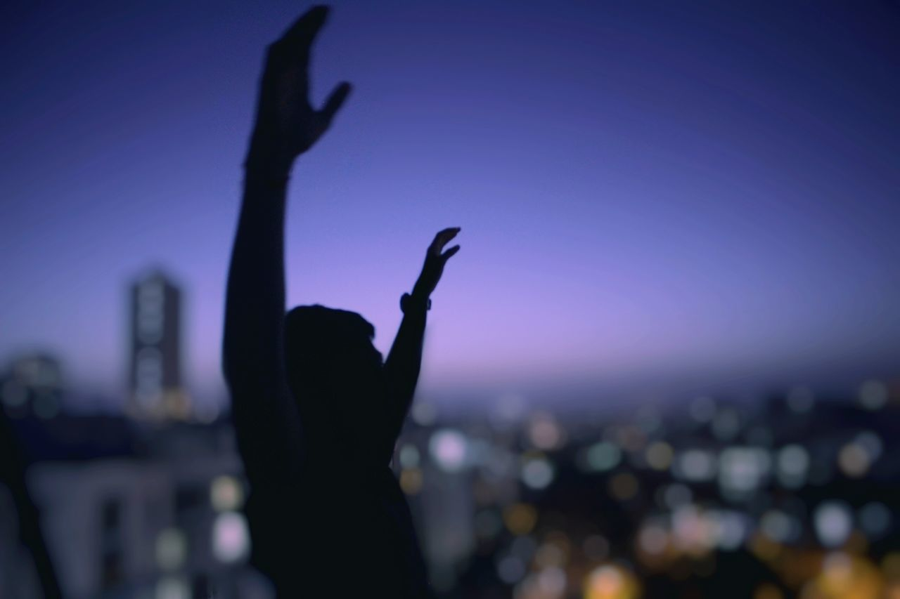 Silhouette man with arms raised against illuminated city at night