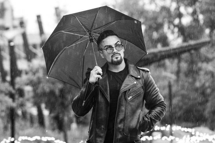 Portrait of man with umbrella standing in the rain