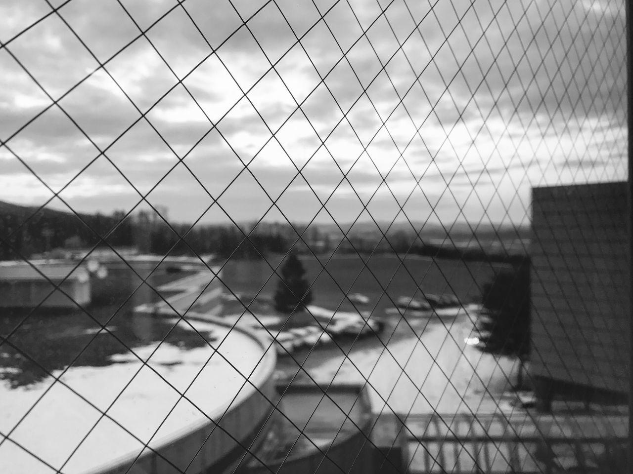 Buildings Seen Through Chainlink Fence Against Cloudy Sky