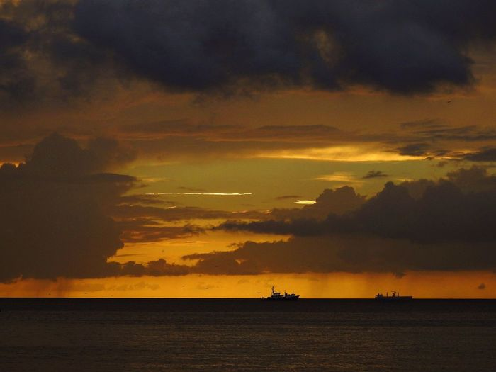 Rain Clouds Boat Sky Water Cloud - Sky Sunset Sea Beauty In Nature Scenics - Nature Orange Color Silhouette Tranquility Horizon Tranquil Scene Nature Horizon Over Water Nautical Vessel Idyllic Land Beach Outdoors