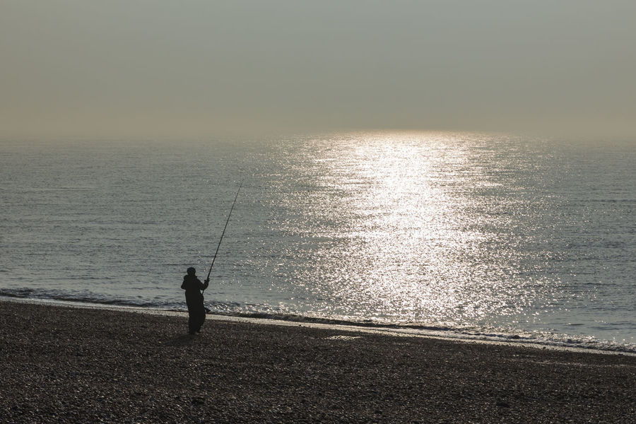 Fishing on the Beach by Dungeness, Romney Marsh, England, United Kingdom Beauty In Nature Fishing Fishing Equipment Fishing Pole Fishing Rod Fishing Tackle Full Length Holding Horizon Over Water Idyllic Leisure Activity Men Nature One Person Outdoors Real People Scenics Sea Silhouette Standing Sunset Tranquil Scene Tranquility Water Weekend Activities