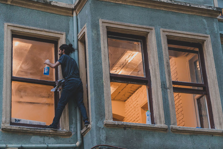 A young man stands on the edge of a high windowsill to wash a window. - IG: @LostBoyMemoirs (All photos taken on Sony A6300 and edited in Lightroom). Istanbul Turkey Turkish EyeEm Best Shots The Week on EyeEm Streetwise Photography Streetphotography Street Photography People People Watching people and places Travel Architecture Built Structure Low Angle View Real People Young Men Dangerous On The Edge The Art Of Street Photography