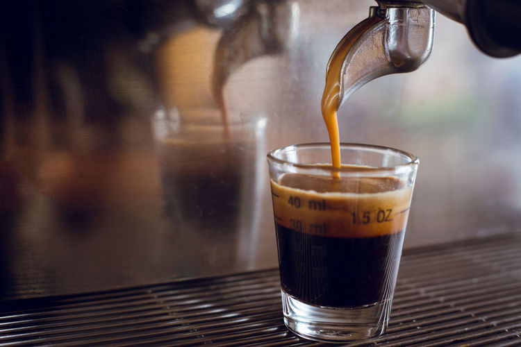 Close-up of glass at espresso machine