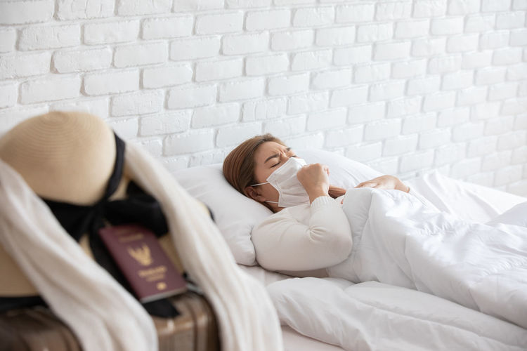 Woman wearing mask while lying on bed at home