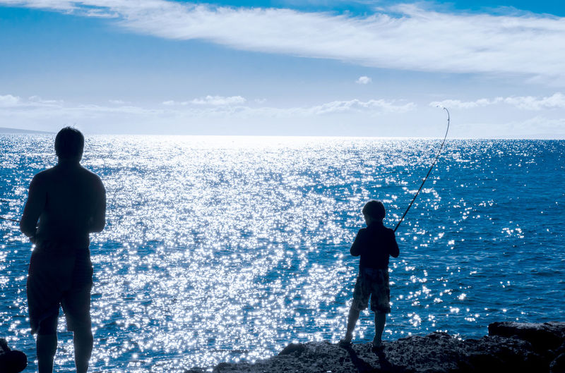 Father and son fishing silhouettes Beauty In Nature Blue Boy Cloud - Sky Day Father & Son Fishing Fun Horizontal Landscape Leisure Activity Men Nature Ocean Outdoor Recreation Outdoors Outdoorsman People Rear View Scenics Seaside Silhouette Sky
