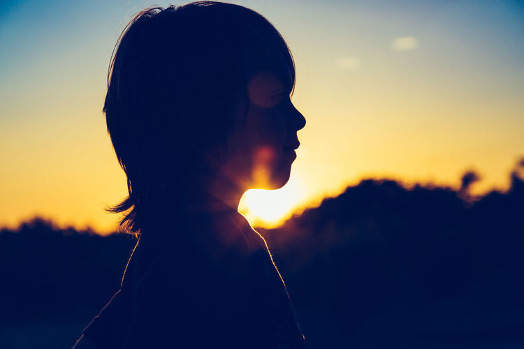 Close-up portrait of silhouette woman against sky during sunset