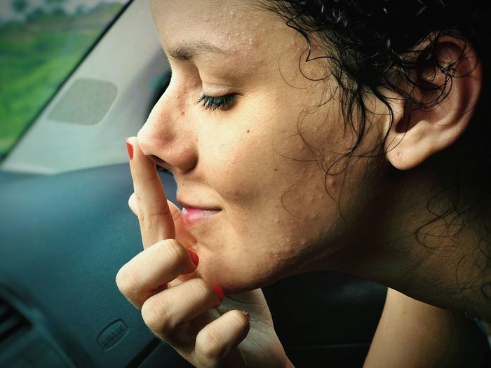 Close-up of woman touching nose in car