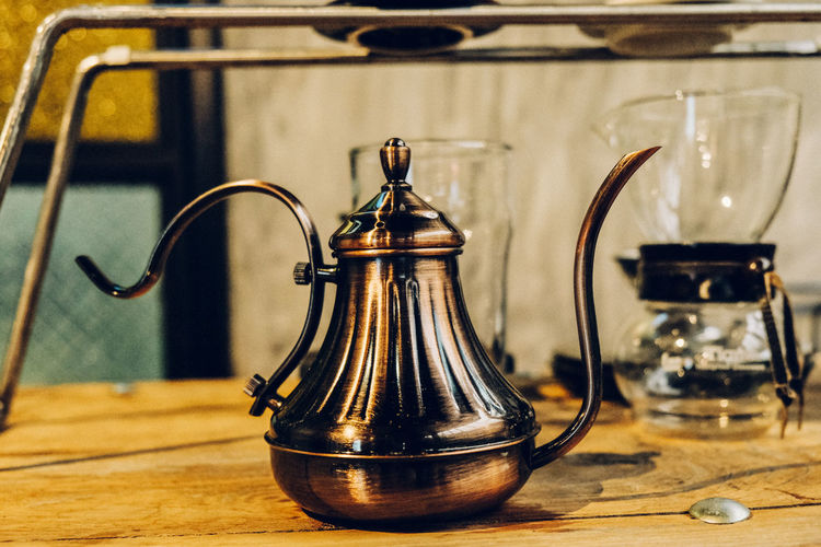 Close-up of antique kettle on table