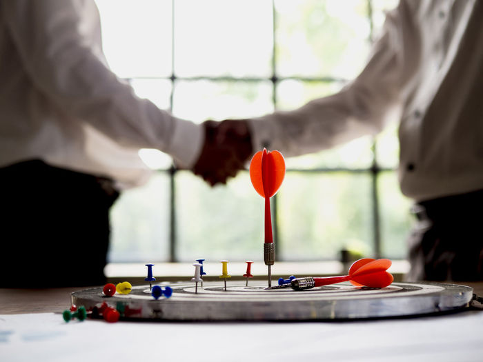 Setting goals for business success and commercial concepts Real People Midsection Men Hand Standing Indoors  Two People Human Hand Human Body Part People Leisure Activity Occupation Playing Selective Focus Table Focus On Foreground Day Adult Arts Culture And Entertainment Lifestyles Finger