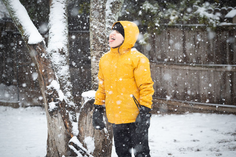 Boy standing on snow covered tree during winter