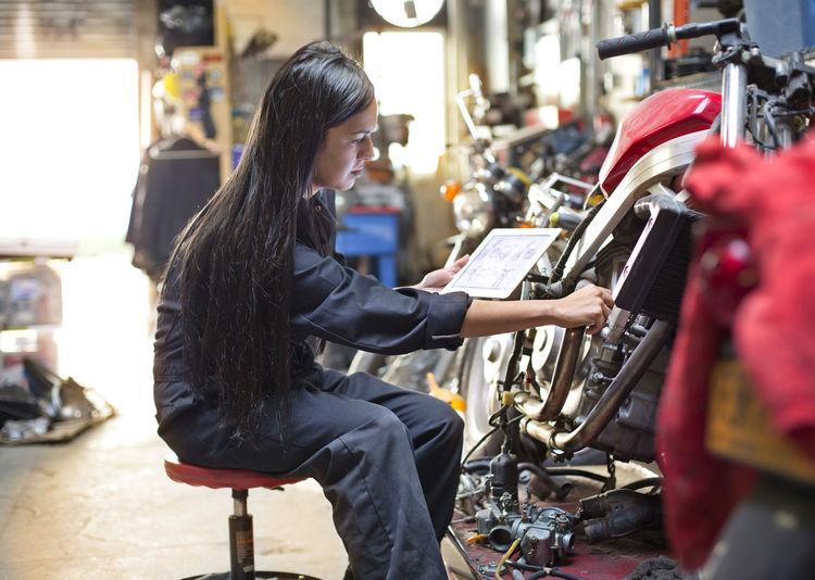 Side view of woman holding digital tablet while repairing bike in workshop