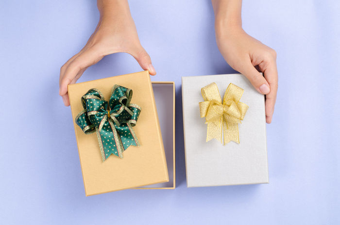 Gift box for giving in holidays Christmas Gift Box Holiday New Year Ribbon X-mas Anniversary Birthday Childhood Close-up Day Directly Above Gift Give Giving Human Body Part Human Hand Indoors  Offer One Person People Present Reward Studio Shot White Background