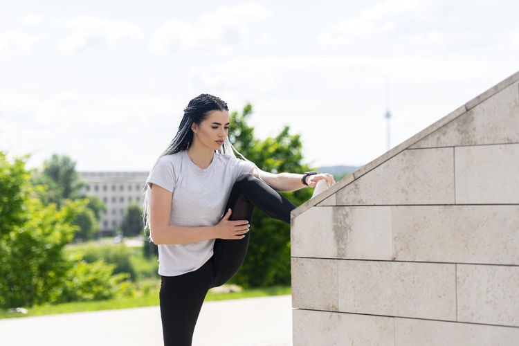 Young woman looking away while standing against built structure
