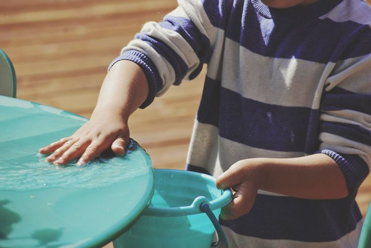 Midsection of boy filling water in bucket