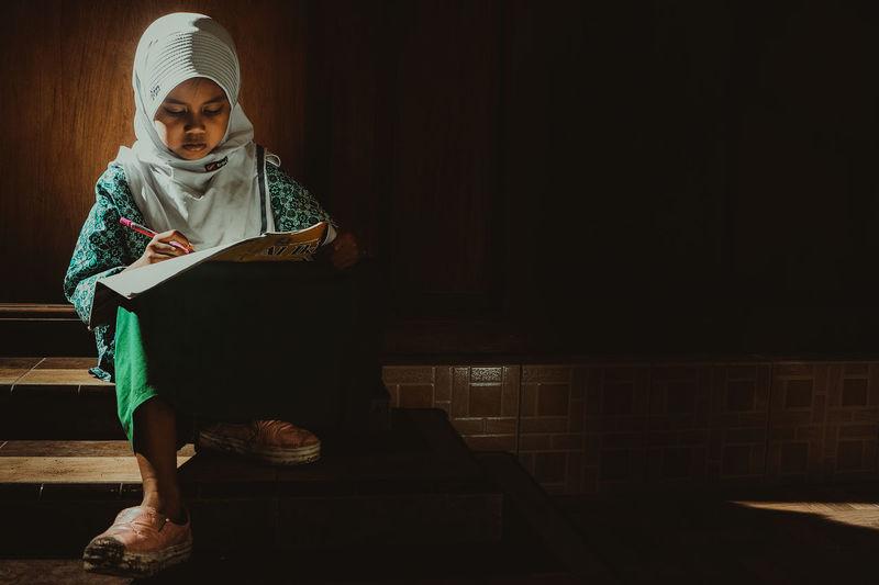 Girl studying in darkroom