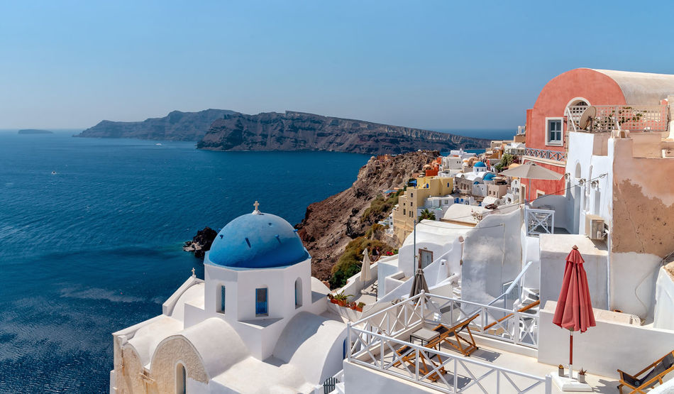View of Oia - Santorini Cyclades Island - Aegean sea - Greece Greece Santorini Oia Island Maditerranean Sea Volcano Caldera Aegean Cyclades Architecture Built Structure Building Exterior Nature Dome Religion Tourism Place Of Worship Mountain Whitewashed Sunlight Belief Travel Travel Destinations Horizon Over Water
