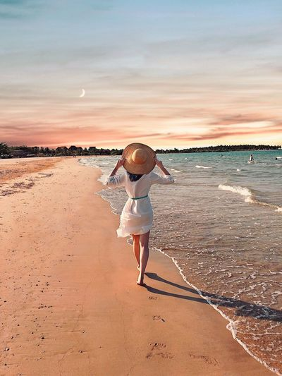 Rear view of woman wearing hat while walking on shore at beach against sky during sunset