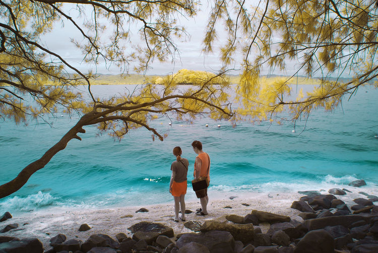 An infrared view of a couple at a beach. Infrared Beach Beauty In Nature Branch Color Infrared Horizon Over Water Infrared Photography Landscape Lifestyles Nature Outdoors People Real People Rear View Rock - Object Scenics Sea Sky Standing Togetherness Two People Vacations