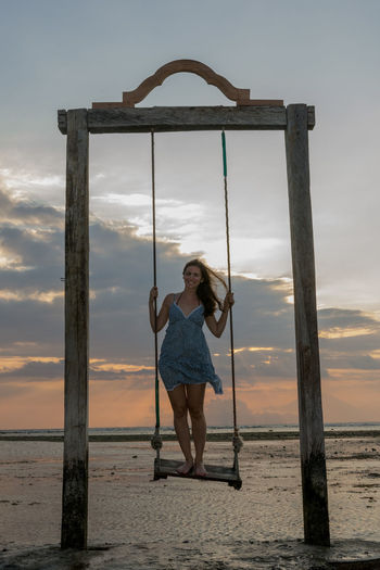 Portrait of happy woman standing on rope swing at beach against sky