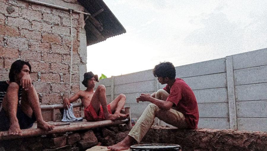 Men sitting on wall against sky