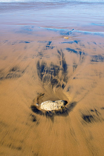 Black pattern marks as water makes patterns in the golden sand in agadir, morocco