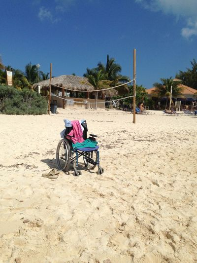 Wheelchair on sand at beach against sky during sunny day