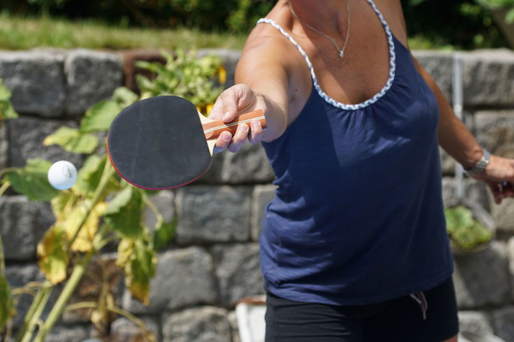 Table Tennis One Person Leisure Activity Standing Holding Lifestyles Day Focus On Foreground Real People Midsection Three Quarter Length Women Front Or Back Yard Casual Clothing Adult Outdoors Nature Front View Playing Motion