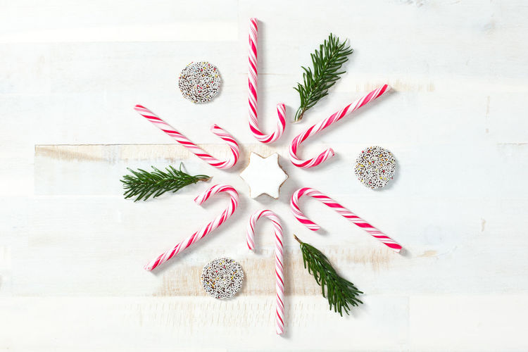 Candy Canes and sweets arrangement on white wood for Christmas Christmas Holidays Sugar Arrangement Candy Candy Cane Conifer  Directly Above Fir Indoors  No People Sugarcane Sweets White Background White Wood